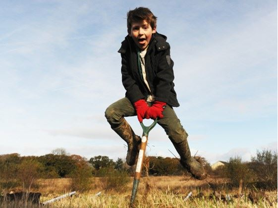 Child jumping with a spade