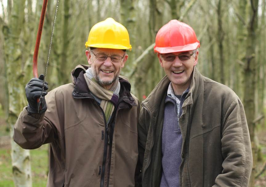 Two smiling volunteers holding up a bowsaw