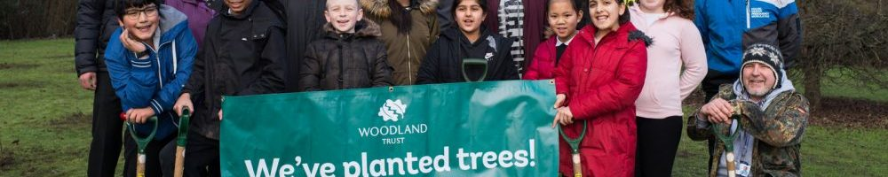 School children holding a banner saying We've planted trees